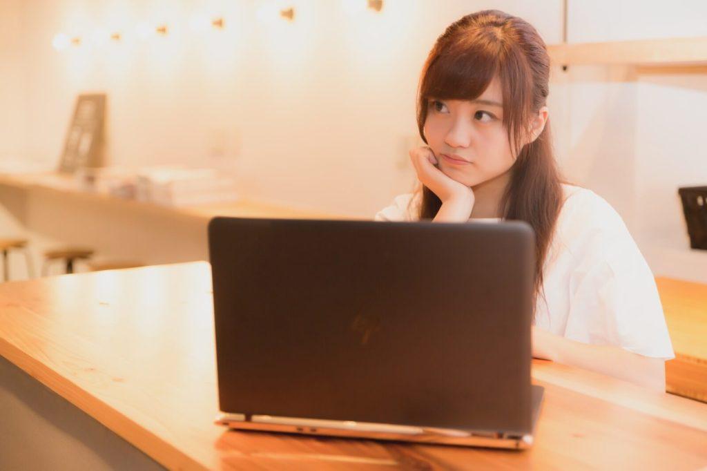 パソコンの前で考える女性